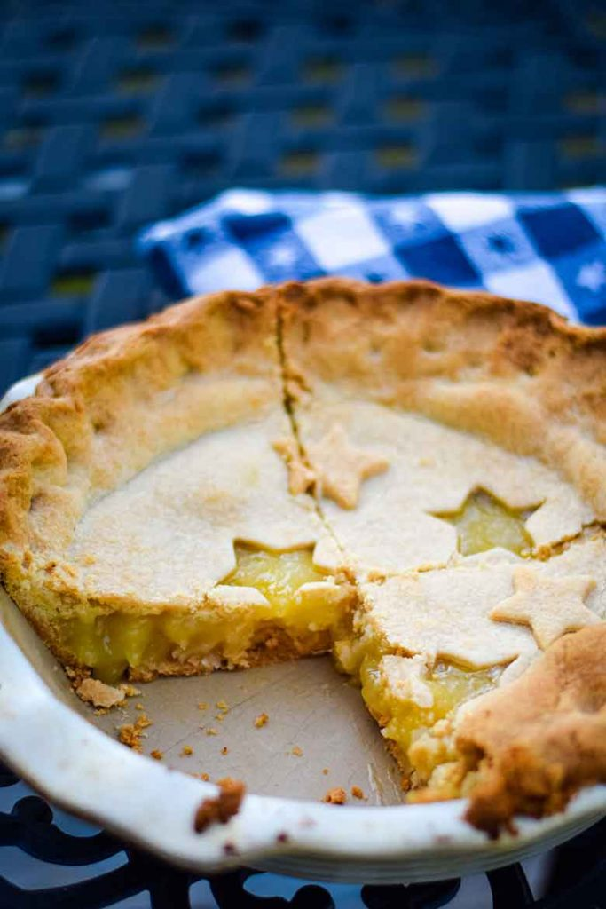 Fully baked Pineapple Pie with two slices cut out, overhead view