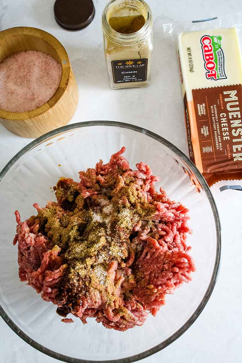 Overhead view of ground beef in mixing bowl with seasoning on top of meat and show of ingredients surrounding the bowl