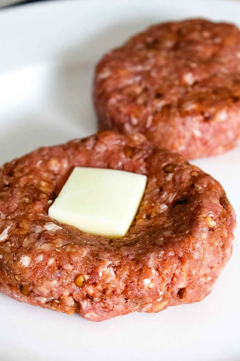 raw burger mix with chunk of Cabot Meunster Cheese in the center prior to shaping the meat around the cheese