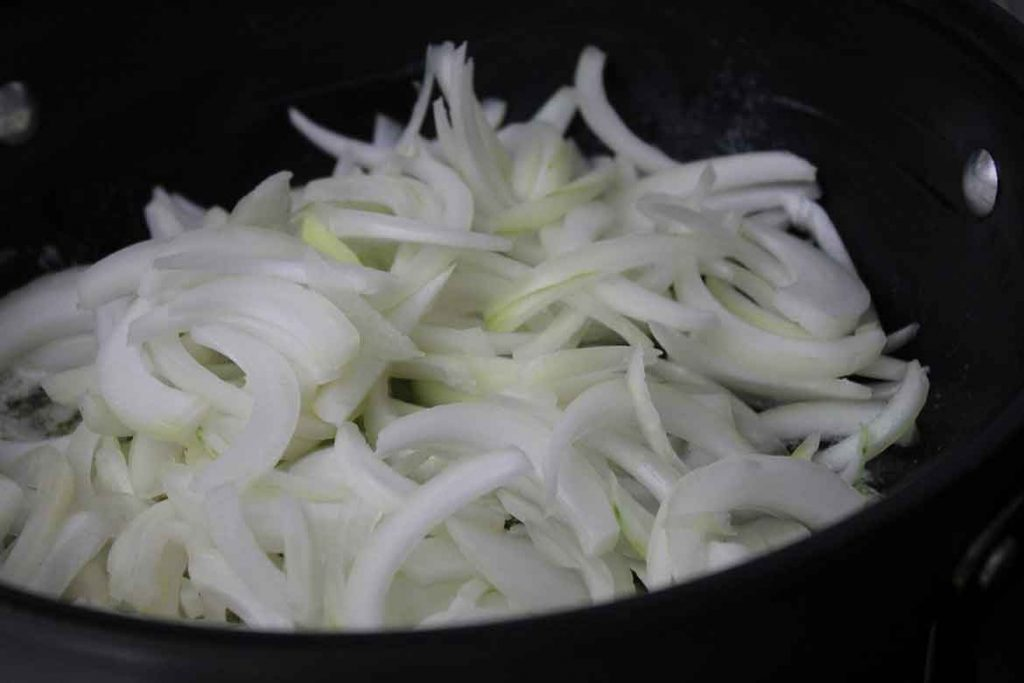 step one - raw onion slices in a skillet on cooktop