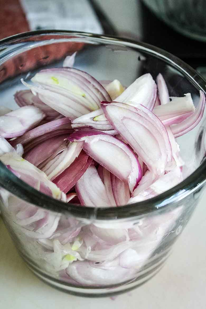 A two cup glass measure filled with sliced shallots
