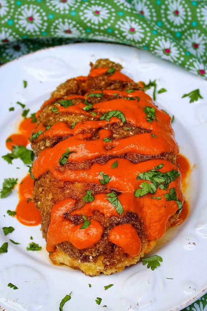 overhead view of blue cheese stuffed chicken with buffalo sauce and cilantro garnish