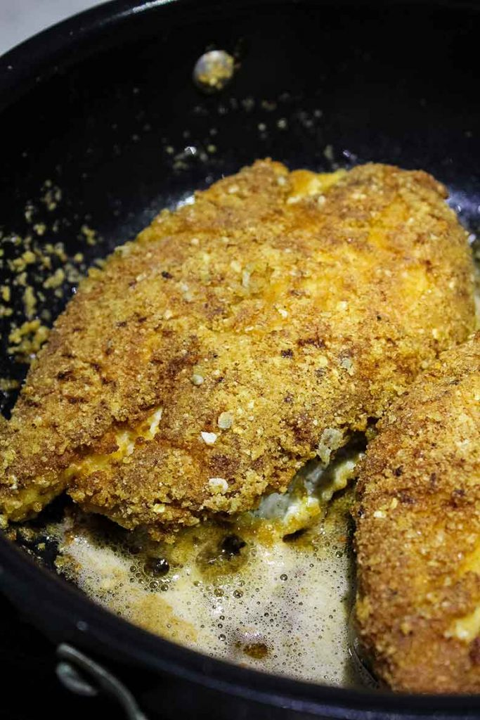 breaded chicken breast cooking in the skillet