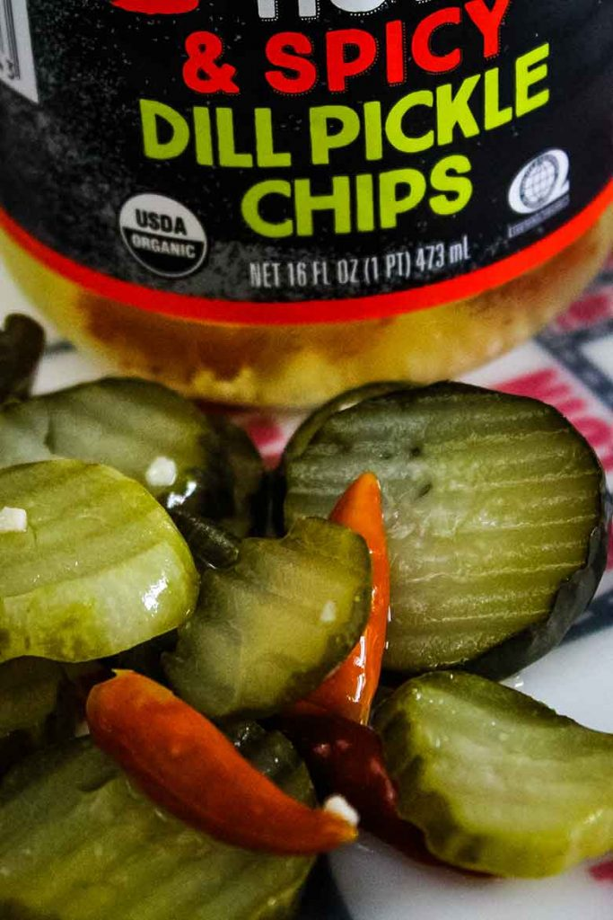 spicy dill pickle chips on cutting mat with jar in the background