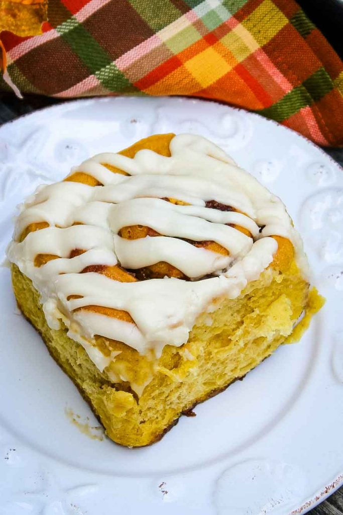 Pumpkin Cinnamon Roll on a plate with an orange and green napkin next to it