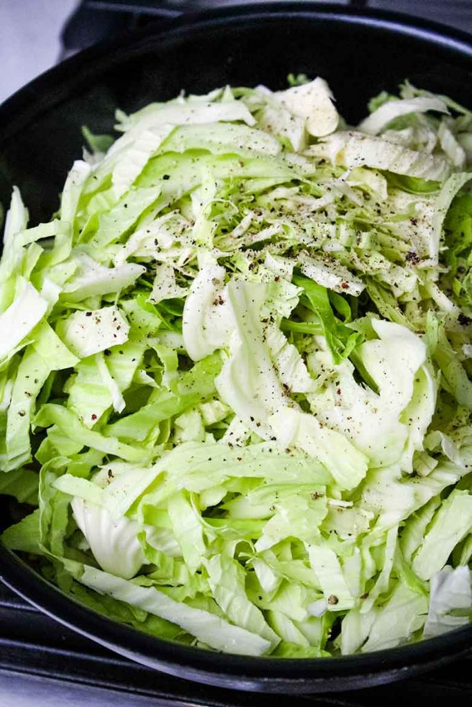 Sliced cabbage in the hot skillet with salt and pepper seasoning sprinkled on top