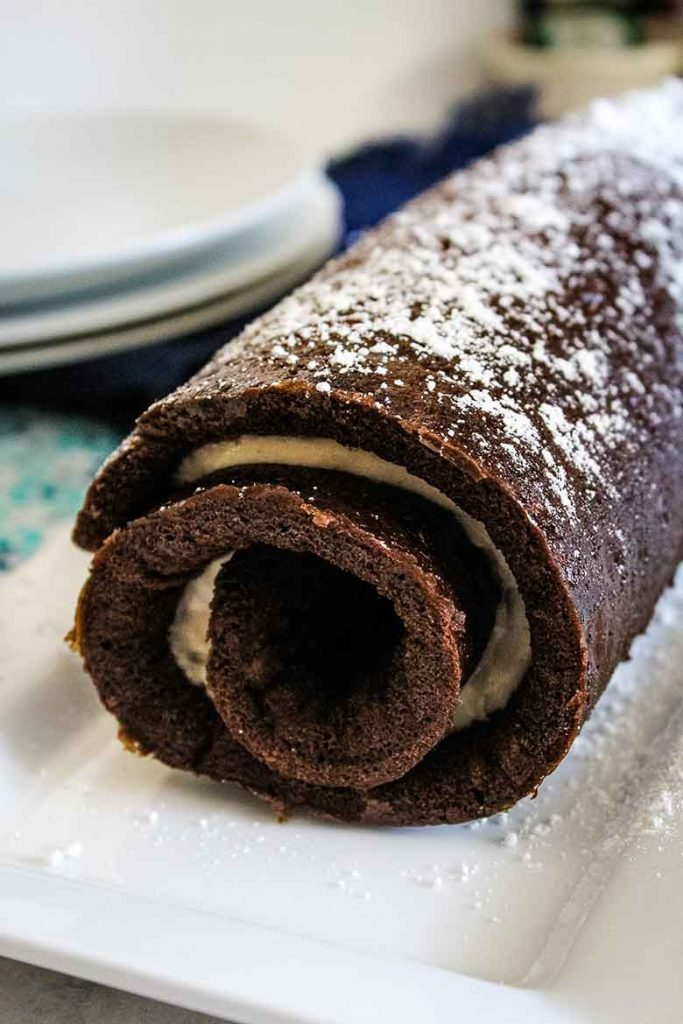 Chocolate Zucchini Cake Roll with Spiced Cream Filling on a serving plate prior to slicing
