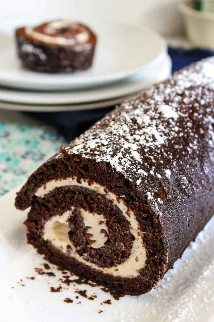 Chocolate Zucchini Cake Roll on a serving platter with a slice of cake in the background