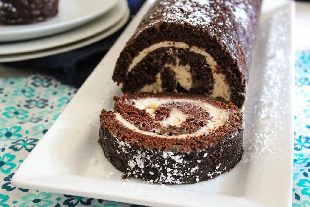 Chocolate Zucchini Cake Roll with a slice on the serving tray and whole roll behind the cake slice
