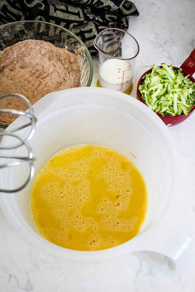 egg mixture with shredded zucchini and flour mixture ready to combine