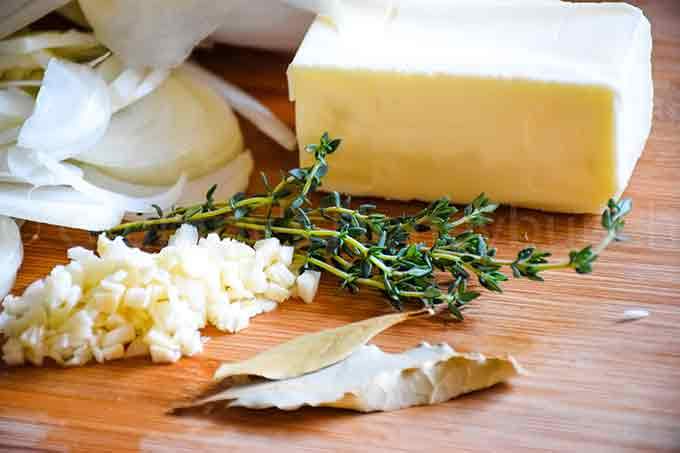 Ingredients for the soup recipe: minced garlic, onion slices, butter, thyme, and bay leaves