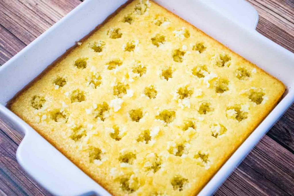 baked yellow cake in a white ceramic baking dish with large holes poked all over the cake