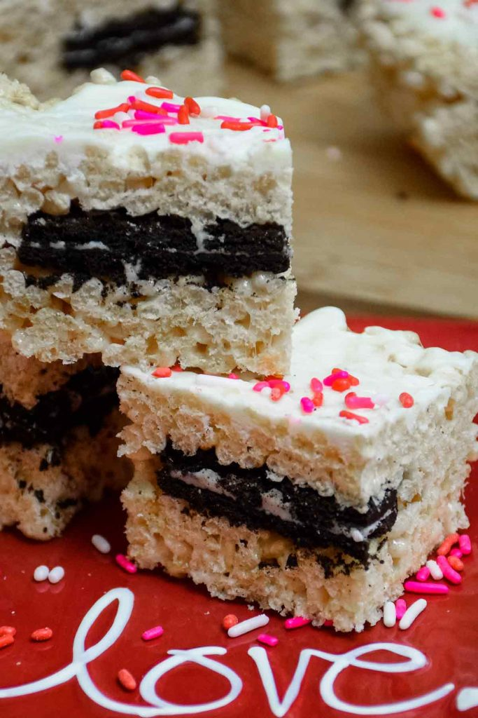 Stacked Oreo Stuffed Rice Krispie Treats on a red plate with the word love
