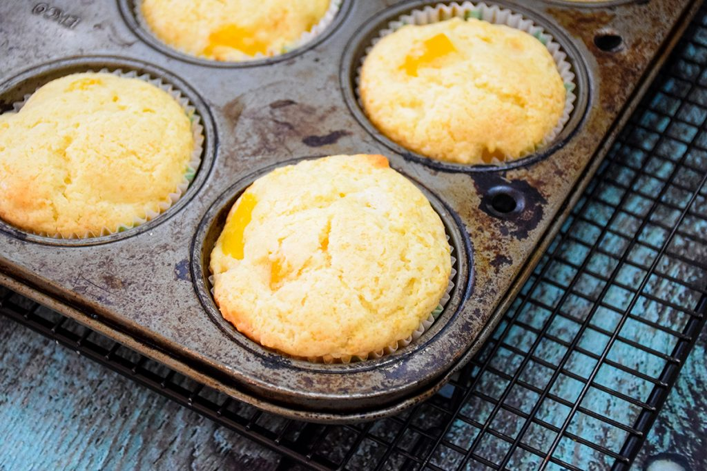 Baked Peach muffins in the pan cooling on a wire rack