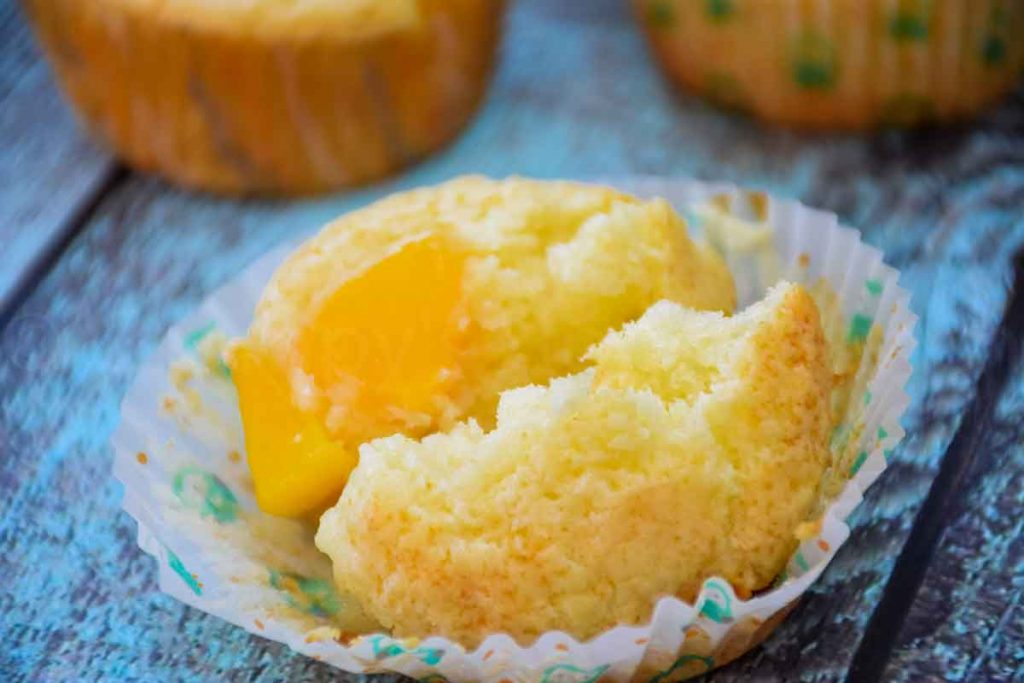 Peach muffin broken in half to show the inside of the muffin