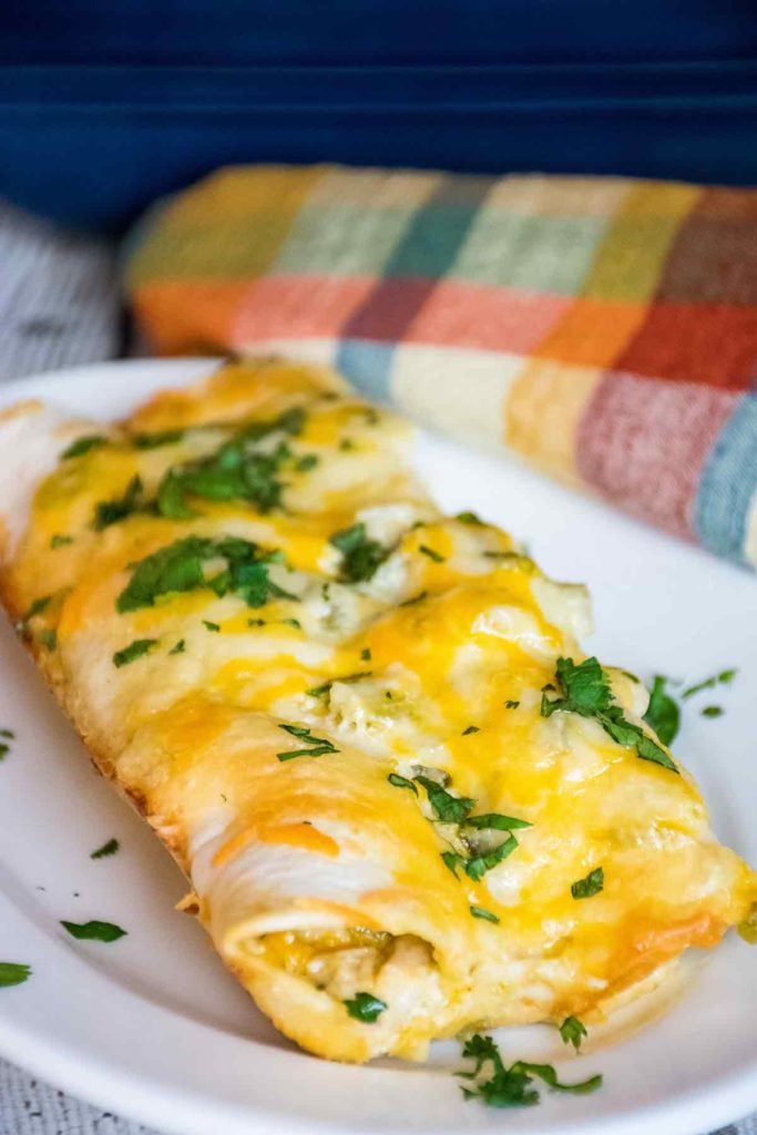 two low carb green chicken enchiladas on a white plate